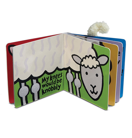 An open paper board book standing up. Opened to green pages with a side view of a white lamb with a grey face and legs. the words My Knees would be knobbly are written in black between the lambs front and rear knees.