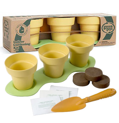 This indoor gardening kit comes complete with pieces of fake dirt, and a shovel. One kit is shown inside its cardboard packaging while the other is shown outside the box with its fake dirt and shovel.
