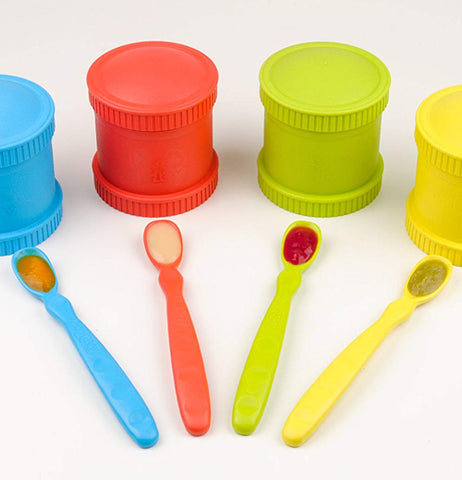 "The Four ""Primary"" Infant Spoons lay on the table with the Four canisters with the same color as the spoons."
