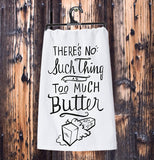 "The white dish towel with the words, ""There's No Such Thing as Too Much Butter"" in black lettering hanging from its black plastic hanger against a wooden wall."