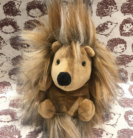 A brown hedgehog plushies has a hairy body and a smooth body. It's facing front, and is on a brown and white hedgehog tablecloth.