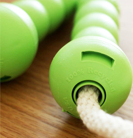 A close-up of the jump rope's green recycled handles is shown.