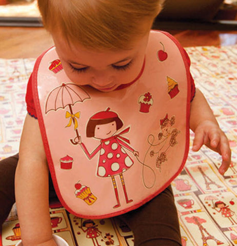 The baby laying on the Jumbo Floor Splat Mat in Cupcake while wearing an apron with the same pattern.