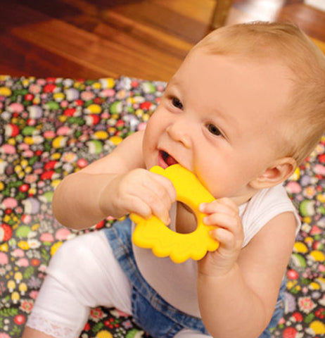 "The baby chewing on a ""Hedgehog"" teether while sitting on the ""Hedgehog"" Jumbo Floor Splat Mat."