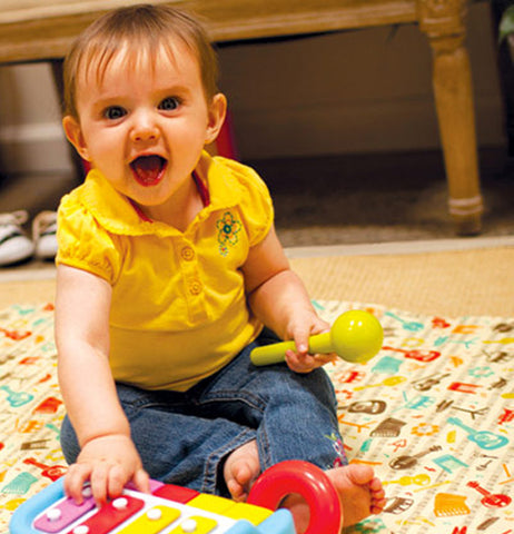 "A baby playing his toy xylophone on the ""Music"" Jumbo Floor Splat Mat."