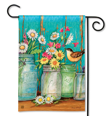 Garden flag that has a blue and brown backgrownd with jars with pink, yellow and white flowers in them and a bird standing on one of the jars in the foreground.