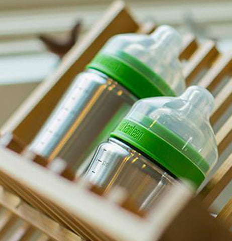 One 5 ounce and one 9 ounce brushed stainless baby bottle sitting on a wood dish drainer. Each bottle has a lid that is green where it screws to the bottle with a clear nipple and clear cover.