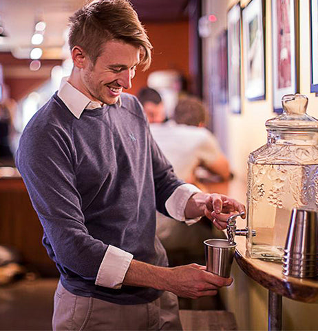 This image shows a young man in a blue sweater pouring water into the steel cup from a glass water dispenser.