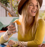 This image shows a young woman in a yellow sweatshirt wearing a hat and holding a lemon in the steel cup.