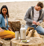 "The woman and man sitting on the beach with their ""Brushed Stainless"" Insulated Growler on the cut tree stump."
