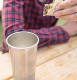 This image shows the cup standing next to a man with a black and red striped sweater eating a taco.