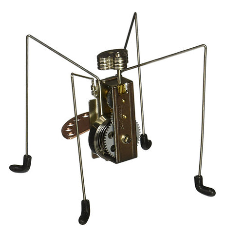 This little metal wind-up toy is shaped like a four-legged spider with a gray metal wind-up handle in the back and black socks on its feet.