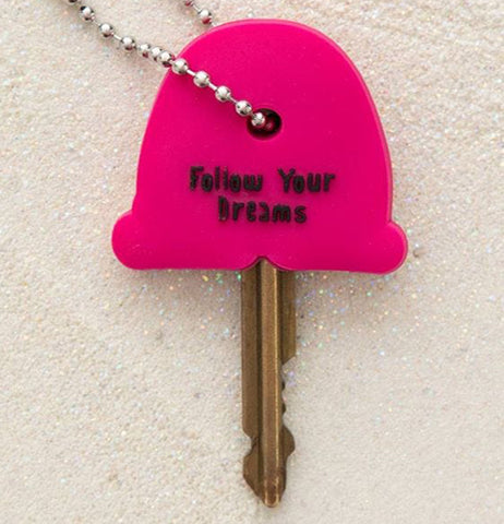 "Pink back of Rainbow key cap with sentiment that reads ""Follow Your Dreams"" on a key."
