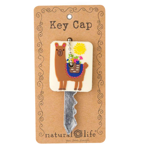 A square white key cap with a brown llama and a sun on it hangs on a brown packaging card with the word key cap at the top and the natural life logo at the bottom.