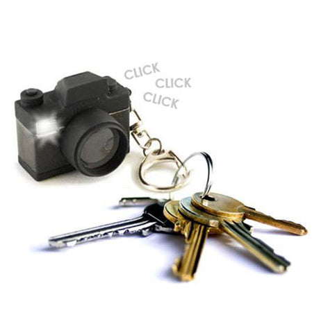 The black camera-shaped keychain is shown attached to a set of different keys.