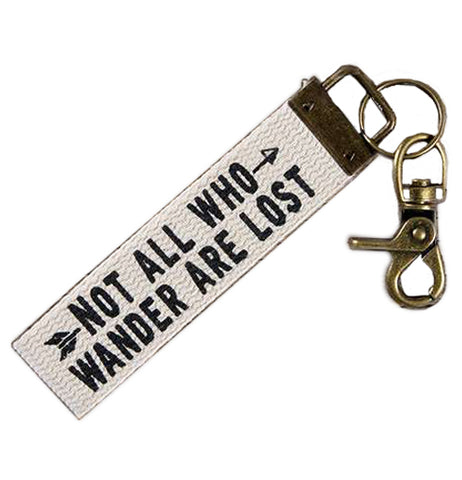 "White canvas key fob that has the words ""Not all who wander are lost"" in black. Attached to one end is a brass key ring and lobster clasp."