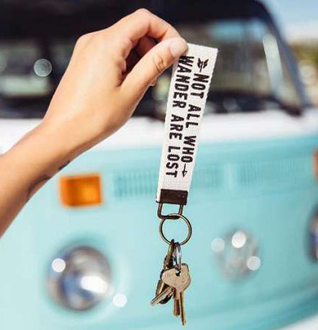 a key fob that says Not All Who Wander Are Lost held up by someone with a blue Volkswagen in the back ground