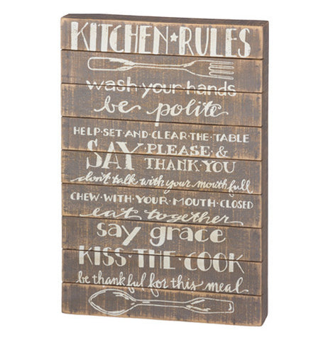 "Slat Sign with ""Kitchen Rules"" written out on it with white letters and a wooden background."