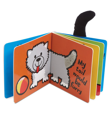 "Two pages of the ""If I Were a Puppy"" book show a white puppy with a yellow and orange ball on an orange background and reads, ""My tail would be furry.."" in black lettering."