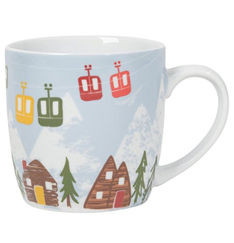 "The Mug ""Hit the Slopes"" has ski lifts hanging over cabins and trees in front of a snowy mountain backdrop."