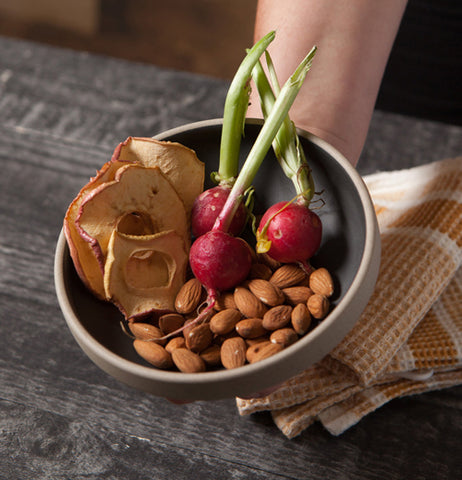 A hand holds a bowl filled with nuts and vegetables over a table.