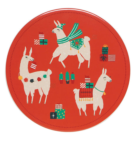 This red trivet features a design of three white llamas wearing different Christmas attire. The first one is wearing a green scarf, a green hat, and a green carpet on its bag. The second is shown with a red carpet on its back with wrapped up Christmas presents and wearing a bell around its neck. The third one has a string of puffballs around its neck and is holding a red and white stocking. In the middle of the trivet are some miniature Christmas trees.