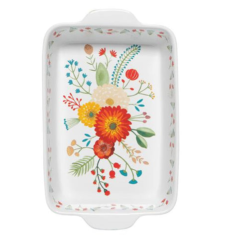 The green baking dish with the white interior decorated with the flower design is shown directly from a downward angle.