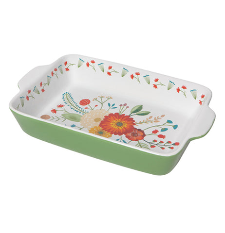 This green baking dish has a white interior decorated with red, white, and orange flowers. Its rim interior is shown decorated with small red flowers and green leaves.