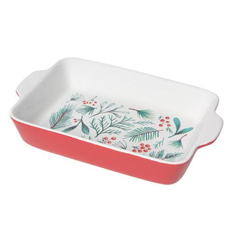 This red baking dish has a white interior decorated with red berries and green pine needles and leaves.