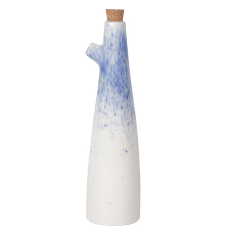 A white oil cruet with a blue section at the top where a cork is able to be removed for filling and spots below for appeal.