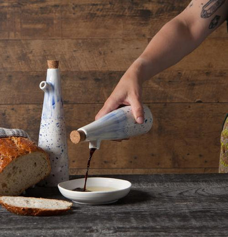 A loaf of bread is on the table, along with a bowl and cruet, while a hand uses another cruet to pour balsamic vinegar into the bowl.