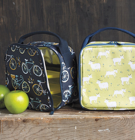 The blue lunch bag covered with bicycles is shown open with a green apple sitting on its left. To the right of the image is another lunchbox with goats against a green background.