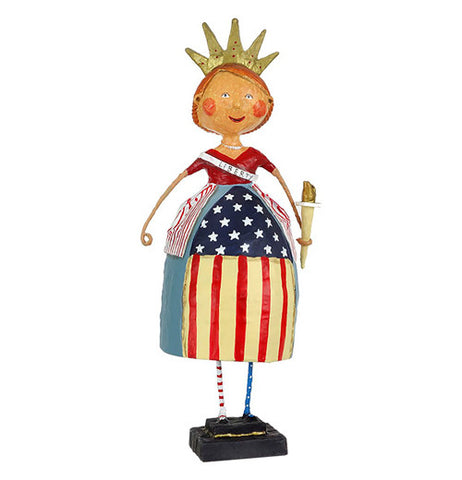 "A smiling woman figurine wears a red, white, and blue, a crown, flaming on top of her head,  a torch on one hand, and  ""liberty"" on her side of the dress."