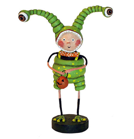 This sculpted figurine is of a child dressed as a green alien with long eye antennae. He holds an orange pail shaped like a jack-o-lantern.