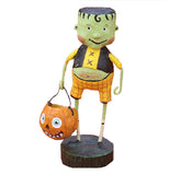 Little Frankie Stein figurine wearing a black and yellow vest and orange checkered pants.  He's carrying a pumpkin candy bucket.