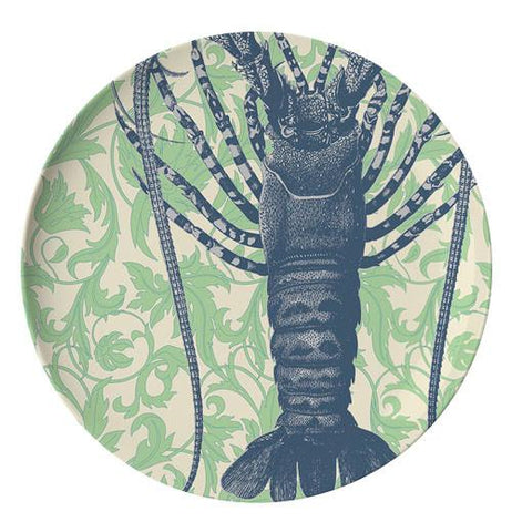 This dinner plate has a design of a dark blue lobster against a green sea grass background.