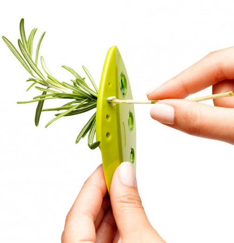 Two hands use a LooseLleaf kale and greens stripper to strip rosemary from the stem.