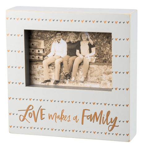 "Box sign with grey and gold heart design and says ""Love makes a family."""