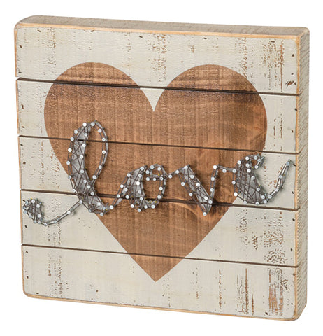"White wooden shiplap box sign with a gold heart in the middle and the word ""Love"" written in string art."