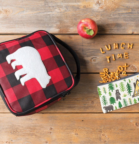 black and red plaid lunch bag with a white bear silhouette is face up on a wood plank background. pretzels spilling out of a pouch spell the words Lunch Time and a red apple sits above.
