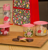 Three different sized glass containers with pink lids and hedgehog designs are shown sitting on a cutting board with cookies on it. A matching lunchbox and water bottle sit behind the cutting board.