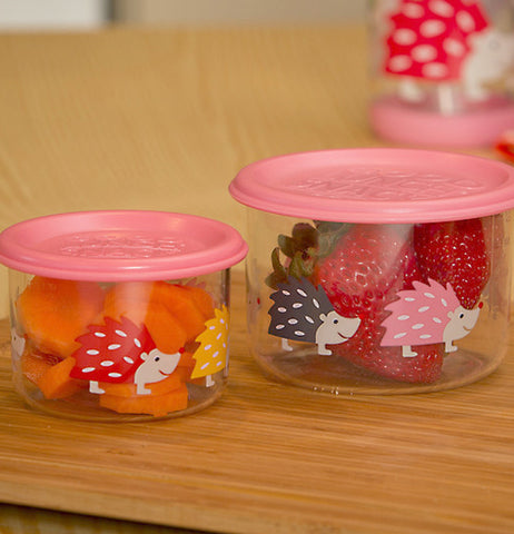 Close up view of the two different sized glass containers with pink lids and hedgehogs on them. Both of them contain fruit, and are sitting on a cutting board.