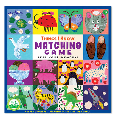 "This memory game has a box with a lid that has panels full of different matching items and animals. The items are shoes, an ice cream bowl, an airplane, and a rocket. The animals include a frog, a ladybug, a butterfly, a cat, a dove, some pigs, penguins, a tiger, a spotted horse, and a dinosaur. In the center of the box are the words, ""Things I Know Matching Game Test Your Memory"" against a white background."