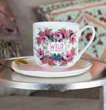 "This ""Wild at Heart"" cup surrounded by red flowers sits on a saucer."