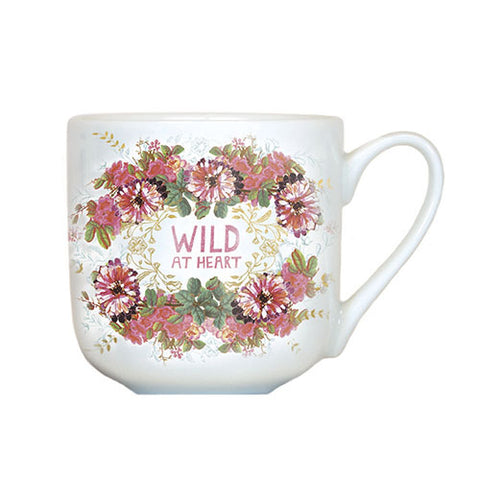 "A white mug with the words ""Wild at Heart"" in the center of a floral pattern."