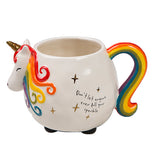 A mug shaped like a unicorn. It has a unicorn head sticking out on one side with a rainbow tail for the handle on the other side.
