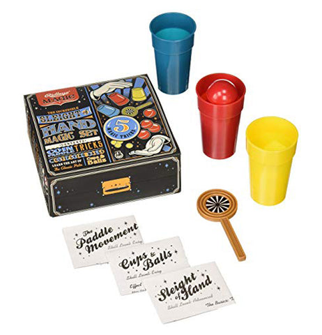 The blue, red, and yellow cups are shown lying next to the box. Below the box are the coin paddle and three white boxes of magic playing cards.