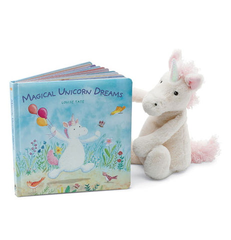 Magical Unicorn Dreams book slightly open standing up next to a white and pink stuffed unicorn.