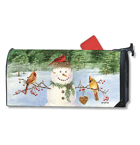 A mailbox cover featuring a snowman with three different colored cardinals perched on him surrounded by snow and green pine trees in background