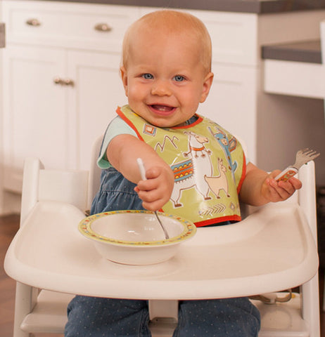 "A baby using his ""Mama Llama"" silverware to eat."